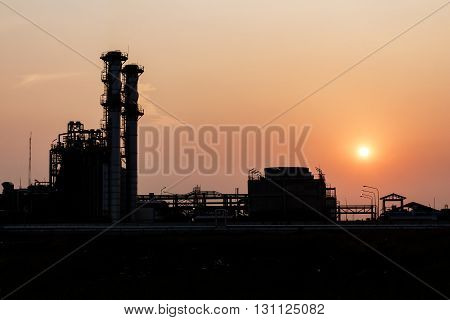 silhouetted of distillation towers at beautiful sunset