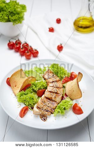 Grilled turkey or chicken breast meat sliced with salad, vegetables, tomatoes, croutons, sesame seeds and sauce. Restaurant menu meal in white dish on table background.