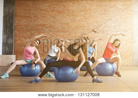 Pretty sporty girls are sitting on fitness balls and exercising. They are stretching arm sideways and smiling