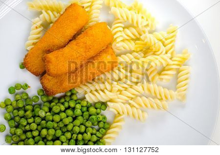 Dinner with fish fingers pasta and peas