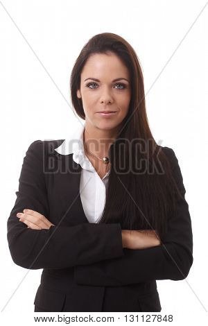 Portrait of confident young businesswoman standing arms crossed, looking at camera.