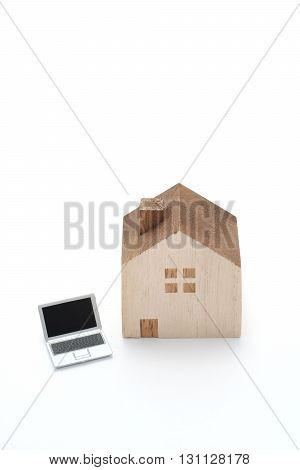 Miniature house and Laptop on white background.