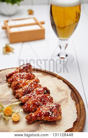 Buffalo chicken wings meat fried in sauce and sesame seeds with glass of beer. Traditional American barbecue restaurant meal.