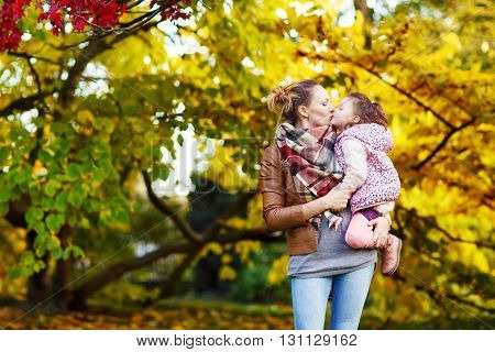 Young mother and her little daughter at beautiful autumn park. Kid girl and woman hugging and kissing. Family portrait outdoors.