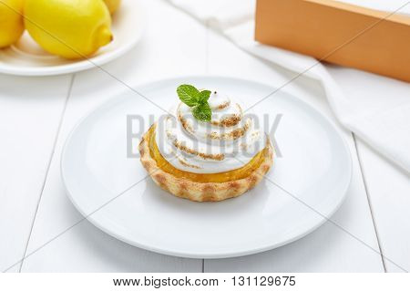 Lemon tart with whipped cream and mint sweet dessert on white plate