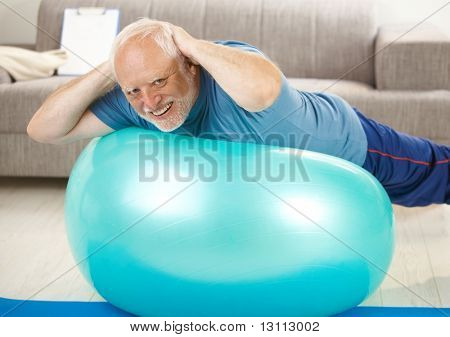 Active senior doing exercises on gym ball at home, hands on nape, smiling at camera.?