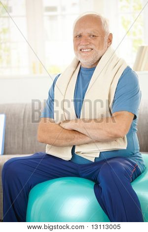 Active senior sitting on fit ball with arms crossed, smiling at camera.?