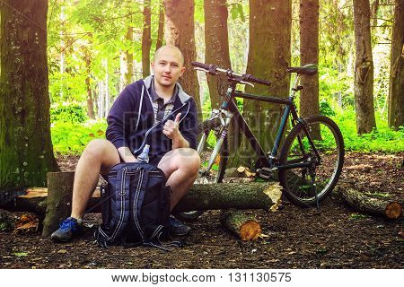 Cyclist with backpack young man holding a water bottle and shows thumb up in beautiful forest summertime journey