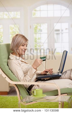 Young woman sitting in armchair at home typing on laptop keyboard, looking at credit card in hand, smiling.?