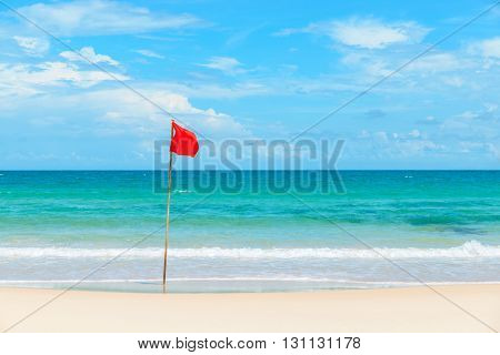 Red flag on tropical beach and azure sea