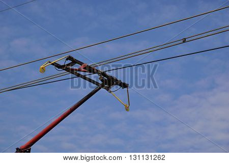 Train pantograph and electric wires against blue sky
