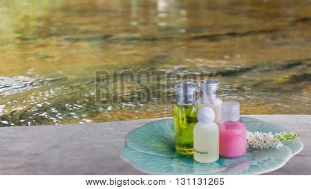 Liquid Soap Gel Bottle Group In Green Plate On Rock With Water Stream Or Surface River Background In