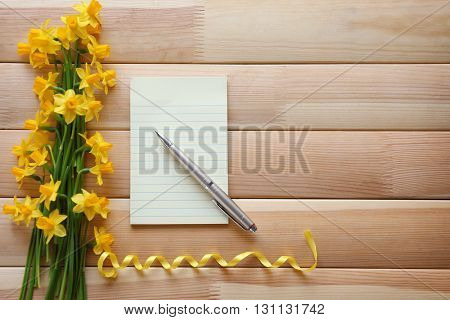 Notebook and yellow daffodils on wooden background