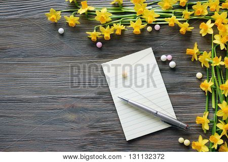 Beautiful narcissus flowers and notebook with pen on wooden table, top view