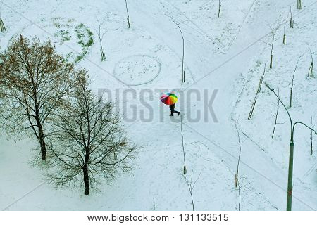 Man walking under colorful umbrella in the snowfall