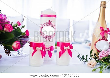 Wedding Candles With Pink Ribbons And Golden Bottle Of Champagne