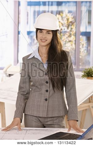 Smart businesswoman with long hair wearing hardhat smiling at camera, standing in bright office.?