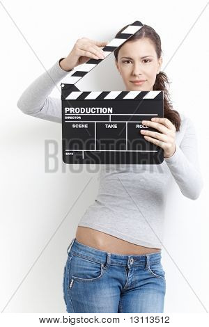 Attractive young female holding clapper board in her hands, front of her face, smiling.?