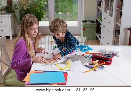 Cute boy and a girl sitting at the table looking at drawings they made. Drawing and cutting paper with scissors. Being creative developing imagination creativity do it yourself concept