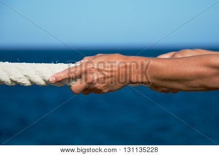 Closeup of woman's hand pulling rope,sea in background