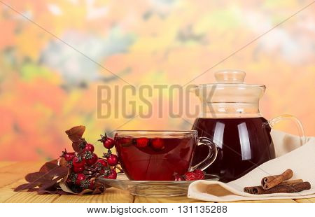 Pitcher and drink a cup of tea rosehip berries on a background of autumn leaves.