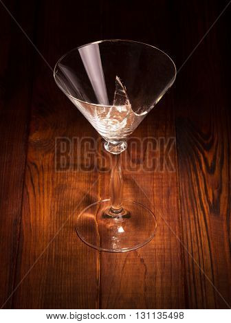 Broken glass of martini on a dark wood background.