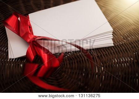 White envelope with red ribbon on wicker basket