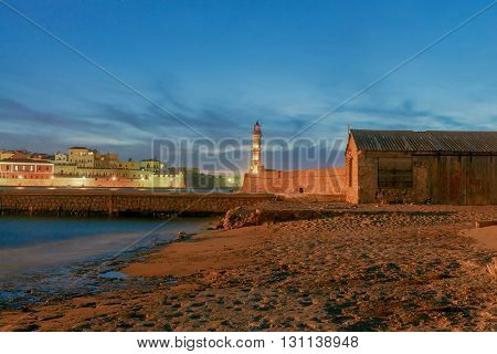 The picturesque view of the old port with lighthouse of Chania in the twilight. Crete, Greece.