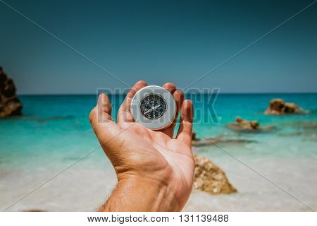 Male hand holding compass at the beautiful beach with the sea in turquoise color in the background