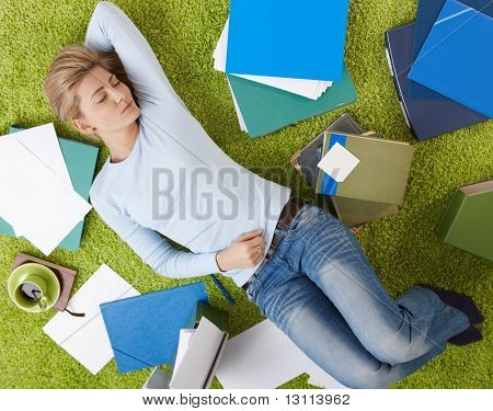 Pretty woman sleeping on floor surrounded with documents in living room floor,  with hand under head.?