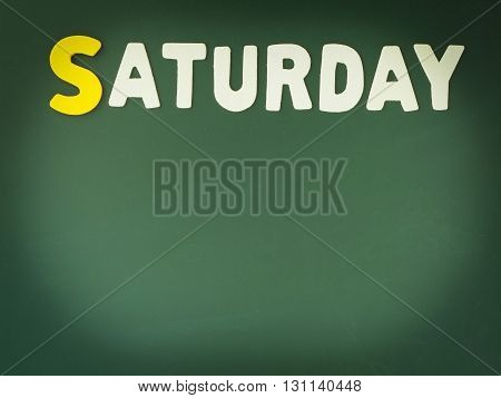 Wooden Saturday on Green Board. Wood Saturday word on blackboard with copy space.