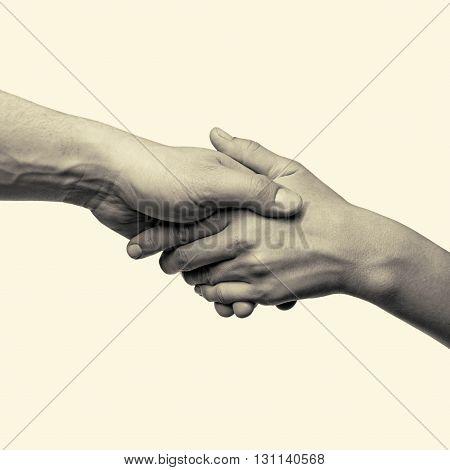 male and female hand united handshake on isolated toned background