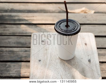 Coffee time. White plastic cup of ice coffee on wooden table. Slow life concept.