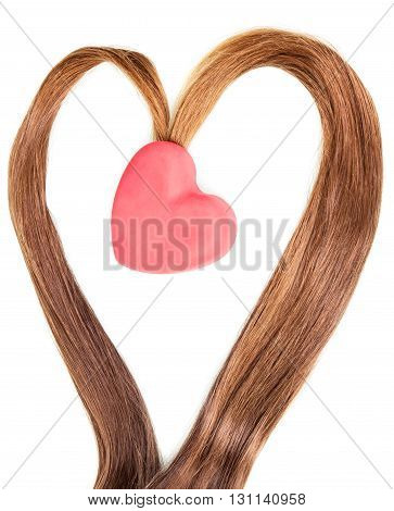 Frame made of strands of brown hair and a red heart isolated on white background.