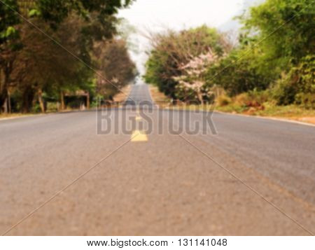 Defocus and blur image of long outback road with trees at wayside. Natural background.