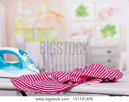 Steam iron and ironing clothes on an ironing board in the room background.