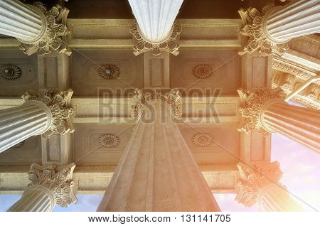 Closeup view of colonnade tops and the decorated ceiling of famous Kazan Cathedral under soft sunlight in Saint-Petersburg Russia.