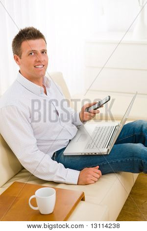 Casual businessman working at home sitting on couch, using laptop computer and mobile phone.?