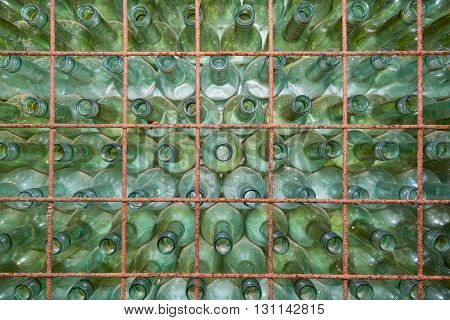 Old used wine bottles stacked in a shelf
