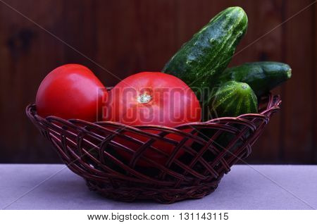 Basket with vegetables. Fresh and wet cucumbers and tomatoes