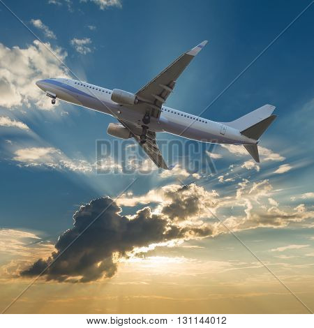 Commercial airplane flying with clouds and sun rays background