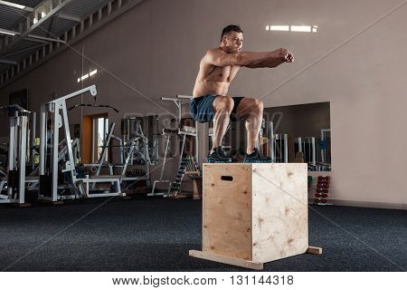 Man box jumping at a crossfit style gym.