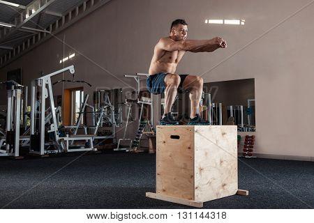 Man box jumping at a crossfit style gym.