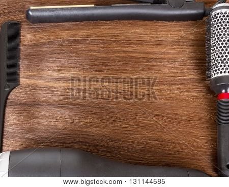 Two combs, hair dryers and curling irons on the background of smooth brown hair.