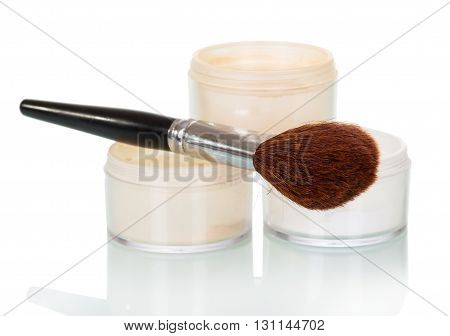 Cosmetic brush and powder jar of face isolated on white background.