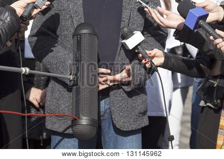 Reporters holding microphones conducting TV or radio interview. News conference.