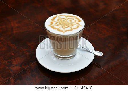 cup of cappuccino with brown and white foam on top