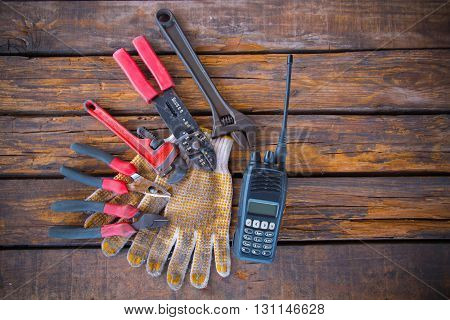Construction tools on a wooden background with walkie-talkie