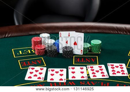 Poker play. Chips and cards on the green table