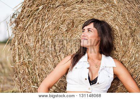 A Happy brunette woman near a haystack.